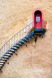 Διακοσμημένα σκαλοπάτια που οδηγούν σε μια πόρτα στον τοίχο τερακότας Στοκ Φωτογραφία