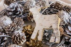 Διακόσμηση κώνων πεύκων με τον ξύλινο χαρασμένο τάρανδο Στοκ Εικόνα