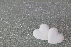2 διαμορφωμένα καρδιά χάπια καραμελών στο ασημένιο υπόβαθρο glittery Στοκ Φωτογραφίες