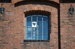 Διαμορφωμένο καρδιά φύλλο του εγγράφου σε ένα μεσαιωνικό παράθυρο δικτυωτού πλέγματος Στοκ Εικόνες
