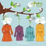 διαμορφώστε την άνοιξη Τα παλτά γυναικών κρεμούν σε έναν κλάδο Στοκ Εικόνες