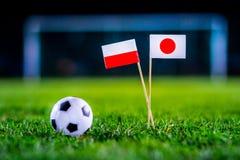 Ιαπωνία - Πολωνία, ομάδα Χ, Πέμπτη, 28 Ποδόσφαιρο Ιουνίου, Παγκόσμιο Κύπελλο, Ρωσία 2018, εθνικές σημαίες στην πράσινη χλόη, άσπρ στοκ εικόνα
