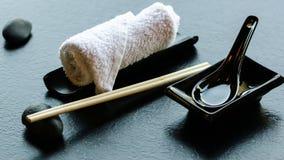 Ιαπωνικά, ασιατικά εργαλεία τροφίμων - ζευγάρι chopsticks, καυτή πετσέτα weat, κεραμικό μαύρο κουτάλι, σκοτεινή πέτρα στο εστιατό Στοκ Φωτογραφία