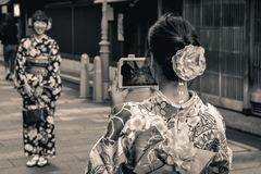 Ιαπωνικά κορίτσια στα παραδοσιακά θερινά yukatas που παίρνουν τις φωτογραφίες το ένα το άλλο με το τελευταίο κινητό τηλέφωνο τεχν στοκ εικόνες