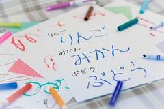 Ιαπωνικά  Παιδιά που γράφουν το όνομα των φρούτων για την πρακτική στοκ εικόνες