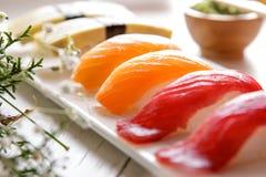 Ιαπωνικά σούσια nigiri κουζινών που τίθενται με το wasabi, τη σάλτσα σόγιας, και το γ Στοκ Φωτογραφίες