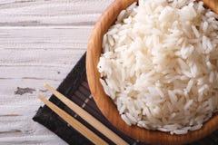 Ιαπωνικά τρόφιμα: βρασμένο στον ατμό ρύζι κατά μια ξύλινη τοπ άποψη κύπελλων Στοκ φωτογραφίες με δικαίωμα ελεύθερης χρήσης