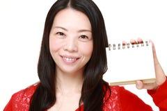 Ιαπωνική γυναίκα που κρατά το κενό σημειωματάριο Στοκ Εικόνες
