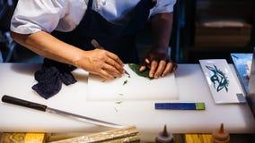 Ιαπωνική δημιουργημένη αρχιμάγειρας τέχνη φύλλων από το μαχαίρι Κόβοντας ένα φύλλο για διακοσμήστε ένα γεύμα στο λευκό πλαστικό τ στοκ φωτογραφίες με δικαίωμα ελεύθερης χρήσης