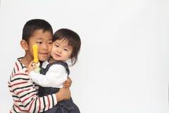 Ιαπωνικοί αδελφός και αδελφή που αγκαλιάζουν η μια την άλλη Στοκ φωτογραφία με δικαίωμα ελεύθερης χρήσης