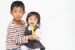 Ιαπωνικοί αδελφός και αδελφή που αγκαλιάζουν η μια την άλλη Στοκ Εικόνα