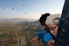 Ιαπωνικοί επιβάτες σε ένα μπαλόνι ζεστού αέρα επάνω από Goreme στην Τουρκία Στοκ Εικόνες