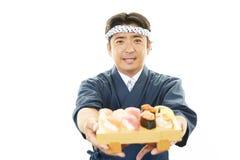 Ιαπωνικός αρχιμάγειρας με ένα πιάτο των σουσιών Στοκ Φωτογραφία