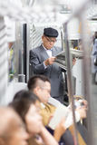 Ιαπωνικός επιχειρηματίας που παίρνει το γύρο στην εργασία το πρωί, που στέκεται μέσα στις δημόσιες συγκοινωνίες και που διαβάζει  Στοκ εικόνα με δικαίωμα ελεύθερης χρήσης