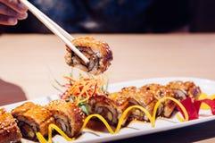 Ιαπωνικός ψημένος στη σχάρα Unagi Maki ρόλος επιλογής με chopstick κοντά επάνω στοκ φωτογραφίες