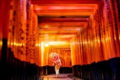 Ιαπωνικό κορίτσι σε Yukata με την κόκκινη ομπρέλα σε Fushimi Inari Shrin στοκ φωτογραφία