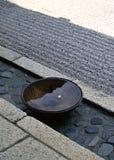 Ιαπωνικό κύπελλο που γεμίζουν με το νερό που κρατιέται σε ένα υπόβαθρο πατωμάτων πετρών στοκ εικόνα με δικαίωμα ελεύθερης χρήσης