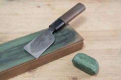 Ιαπωνικό μαχαίρι τεχνών δέρματος σε ένα λουρί μαχαιριών δέρματος με την πράσινη γυαλίζοντας ένωση σε μια ξύλινη επιφάνεια Στοκ Εικόνες