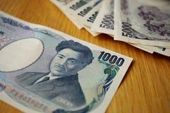 Ιαπωνικό νόμισμα (γεν) με τα ασιατικά σύμβολά του στα τραπεζογραμμάτια μορφής στο ξύλινο υπόβαθρο Στοκ φωτογραφία με δικαίωμα ελεύθερης χρήσης