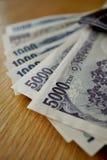 Ιαπωνικό νόμισμα (γεν) με τα ασιατικά σύμβολά του στα τραπεζογραμμάτια μορφής στο ξύλινο υπόβαθρο Στοκ Εικόνες