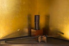 Ιαπωνικό ξίφος Σαμουράι και ιαπωνικό μαύρο κυλινδρικό βάζο με το ηλέκτρινο υπόβαθρο στοκ εικόνα με δικαίωμα ελεύθερης χρήσης
