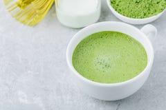 Ιαπωνικό πράσινο τσάι matcha latte στο άσπρο φλυτζάνι στο γκρίζο υπόβαθρο Στοκ Εικόνες