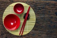 Ιαπωνικό σύνολο σκευών για την κουζίνα κόκκινων chopsticks, κύπελλων και φλυτζανιού στο χαλί μπαμπού και το ξύλινο επιτραπέζιο υπ Στοκ εικόνες με δικαίωμα ελεύθερης χρήσης