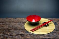 Ιαπωνικό σύνολο σκευών για την κουζίνα κόκκινων chopsticks, κύπελλων και φλυτζανιού στο χαλί μπαμπού στον ξύλινο πίνακα Στοκ Εικόνα