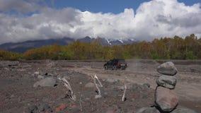 Ιαπωνικό SUV οδηγά στο δρόμο υποστηριγμάτων στον ηφαιστειακό ξηρό ποταμό στην κατεύθυνση του ηφαιστείου φιλμ μικρού μήκους