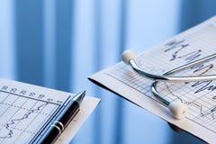 ιατρικά εργαλεία Στηθοσκόπιο και καρδιογράφημα σε έναν πίνακα Στοκ Εικόνα