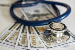 Ιατρικά τοποθετημένα ακουστικά χρήματα δολαρίων, στο γραφείο στοκ εικόνες