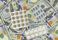 Ιατρικά φάρμακα και ΑΜΕΡΙΚΑΝΙΚΑ δολάρια σε μια άσπρη κινηματογράφηση σε πρώτο πλάνο ανασκόπησης S Δολάρια Στοκ Εικόνα