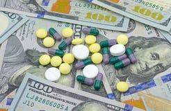 Ιατρικά φάρμακα και ΑΜΕΡΙΚΑΝΙΚΑ δολάρια σε μια άσπρη κινηματογράφηση σε πρώτο πλάνο ανασκόπησης S Δολάρια Στοκ Εικόνες