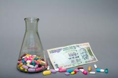 Ιατρικά χάπια στα διαφορετικά χρώματα και τα χρήματα Στοκ Εικόνες