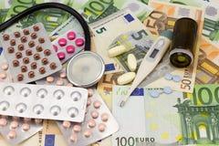 Ιατρικά χάπια, στηθοσκόπιο και θερμόμετρο στο ευρο- υπόβαθρο χρημάτων ως σύμβολο των δαπανών υγειονομικής περίθαλψης στοκ εικόνα