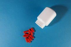Ιατρικές βιταμίνες χαπιών με το πλαστικό άσπρο βάζο Στοκ Εικόνες