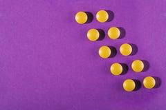 Ιατρικές βιταμίνες χαπιών σε ένα χρωματισμένο υπόβαθρο Στοκ Εικόνες