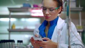 Ιατρική δακτυλογράφηση επιστημόνων στο τηλέφωνο στο εργαστήριο Τεχνικός εργαστηρίων που χρησιμοποιεί το τηλέφωνο στο εργαστήριο φιλμ μικρού μήκους