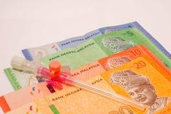 Ιατρική βελόνα πεταλούδων στα τραπεζογραμμάτια της Μαλαισίας που απομονώνονται στο λευκό Στοκ Εικόνες