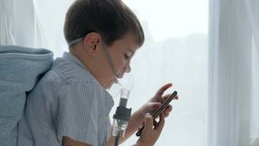 Ιατρική θεραπεία εάν δυσκολία που αναπνέει, παιδί στη μάσκα από nebulizers με το smartphone στα χέρια φιλμ μικρού μήκους