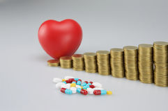 Ιατρική και θαμπάδα των νομισμάτων σωρών με την καρδιά στοκ φωτογραφία με δικαίωμα ελεύθερης χρήσης