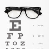 Ιατρική και ιατρικά σύμβολα - κλείστε αυξημένος ενός πίνακα για τη δοκιμή όρασης με τα γυαλιά πέρα από την στοκ εικόνες με δικαίωμα ελεύθερης χρήσης