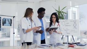 Ιατρική ομάδα, δύο γυναίκες και ένας αφρικανικός άνδρας που στέκονται και συζητούν τη διάγνωση του ασθενή στο νοσοκομείο Ομάδα ια φιλμ μικρού μήκους
