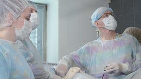 Ιατρική ομάδα που εκτελεί τη χειρουργική λειτουργία στο φωτεινό σύγχρονο λειτουργούν δωμάτιο φιλμ μικρού μήκους