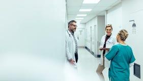 Ιατρική ομάδα που συζητά στο διάδρομο στο νοσοκομείο στοκ εικόνες