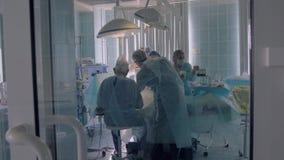 Ιατρική ομάδα νοσοκομείων που εκτελεί τη χειρουργική επέμβαση στο λειτουργούν δωμάτιο απόθεμα βίντεο