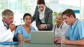 Ιατρική ομάδα που εξετάζει το φορητό προσωπικό υπολογιστή κατά τη διάρκεια της συνεδρίασης απόθεμα βίντεο