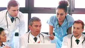 Ιατρική ομάδα που μιλά μαζί lap-top φιλμ μικρού μήκους