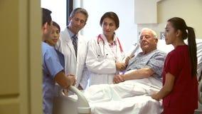 Ιατρική ομάδα που μιλά στον ανώτερο αρσενικό ασθενή στο νοσοκομείο απόθεμα βίντεο