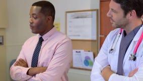 Ιατρική ομάδα που μιλά στον ανώτερο θηλυκό ασθενή στο νοσοκομείο απόθεμα βίντεο